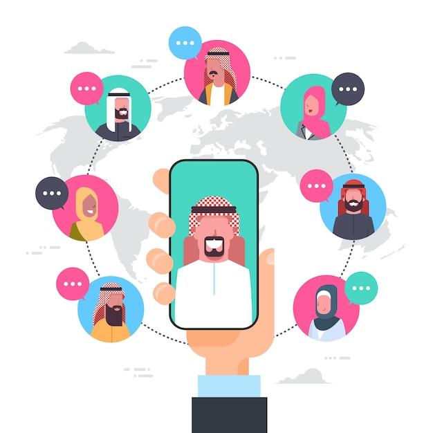 Arabische mann-hand, die intelligente telefonnetz-kommunikations-konzept-gruppe der arabischen leute-verbindung über weltkarte hält Premium Vektoren