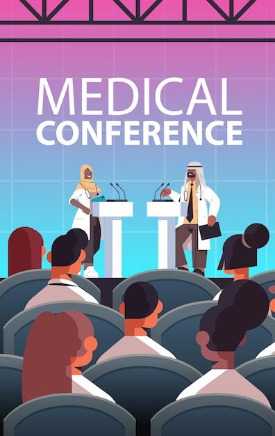 Arabisches ärztepaar, das rede an der tribüne mit mikrofon-medizinischer konferenzbesprechung medizingesundheitskonzept hörsaalinnenraum vertikale vertikale vektorillustration hält Premium Vektoren