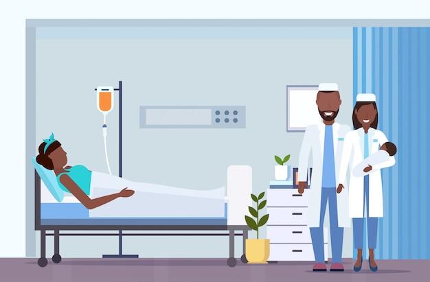 Arzt mit krankenschwester hält neugeborenes baby nahe mutter, die im bett mit droppergeburtskonzept liegt moderne moderne entbindungsstation postnatale abteilungsrauminnenraum horizontale volle länge Premium Vektoren