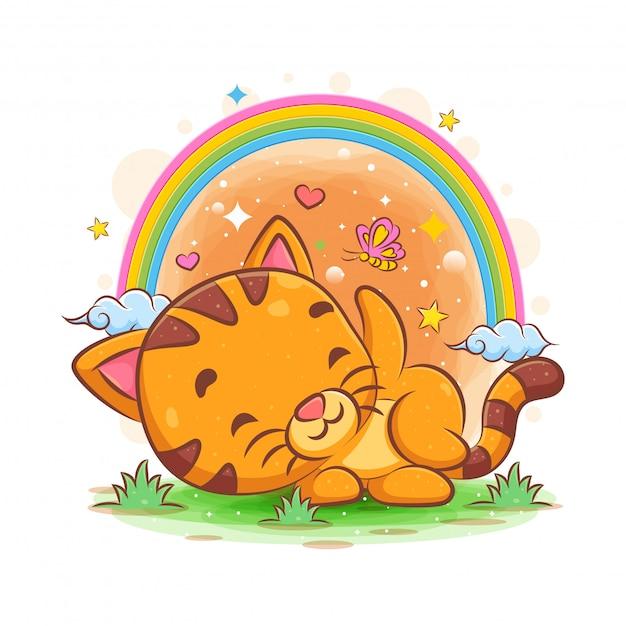 Babykatze, die im garten mit regenbogengarten schläft Premium Vektoren