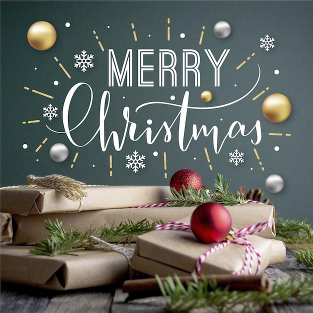 Beschriftung der frohen weihnachten auf weihnachtsfoto mit geschenken und kugeln Kostenlosen Vektoren