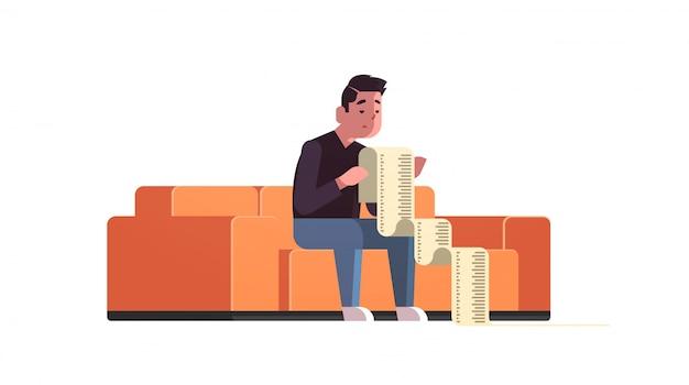 Betonter geschäftsmann mit langem steuerdokumentschuldner entsetzt durch zahlungsrechnungen finanzkrise-konkurskonzept bankrottes sitzen auf dem sofa gesorgt um das zahlen viel geldes horizontal Premium Vektoren