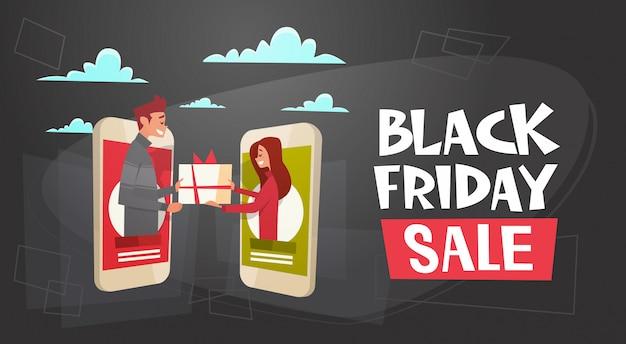 Black friday-verkaufs-fahne mit dem mann, der frauen-präsentkarton durch digital-tablet gibt Premium Vektoren