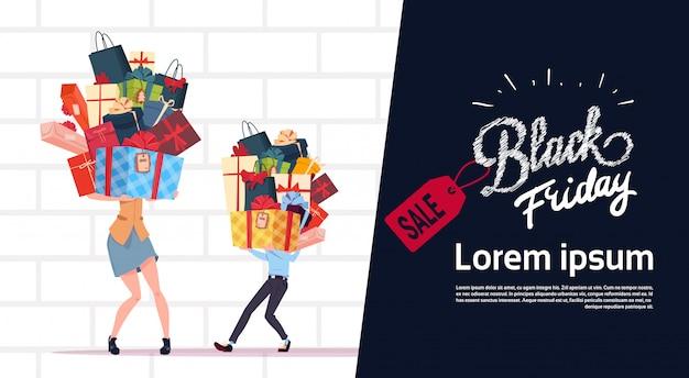 Black friday-verkaufs-plakat mit den paaren, die geschenkboxen über weißem backsteinmauer-hintergrund halten Premium Vektoren