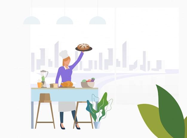 Chef, der abendessen am küchentisch kocht und torte hält Kostenlosen Vektoren