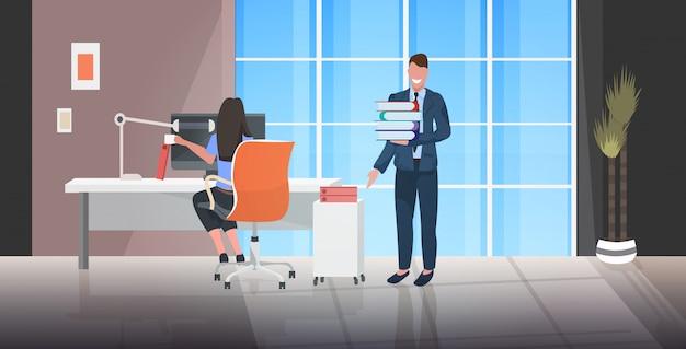 Chef gibt dokumentenstapel an überarbeitete arbeitnehmerin Premium Vektoren