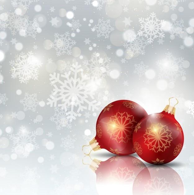 Christmas ball auf einem hintergrund mit schneeflocken Kostenlosen Vektoren