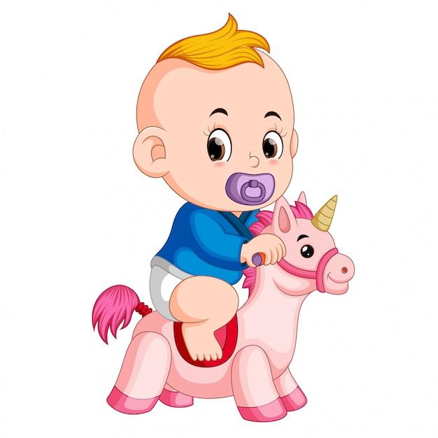 Das baby spielt mit einhornspielzeug Premium Vektoren