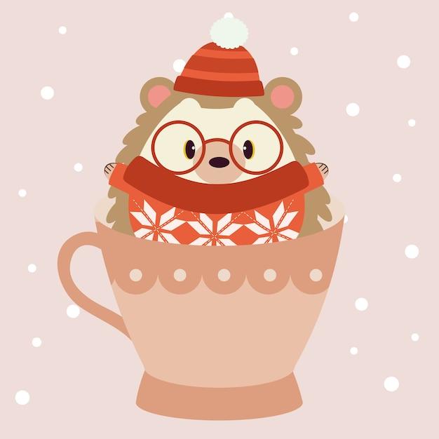 Der charakter des niedlichen igels trägt einen roten winterhut und eine große brille und einen roten pullover und sitzt in der großen rosa tasse Premium Vektoren