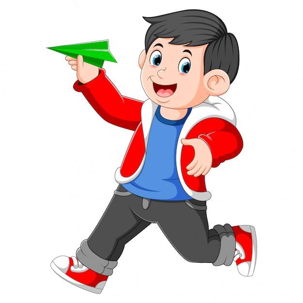 Der junge mit der roten jacke hält das grüne papierflugzeug in der hand Premium Vektoren