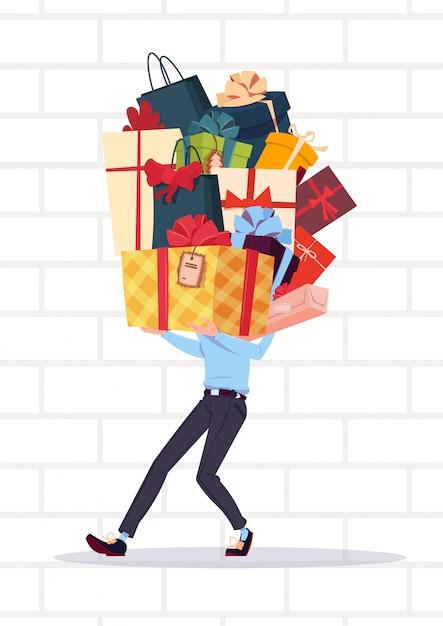 Der mann, der geschenkboxen stapelt, über weißem backsteinmauer-hintergrund-feiertags-geschenk-konzept Premium Vektoren