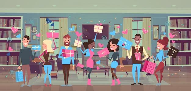 Die gruppe von personen, die geschenkboxen über herzen hält, formt männer und frauen-valentinsgruß-tagespartei-feier Premium Vektoren