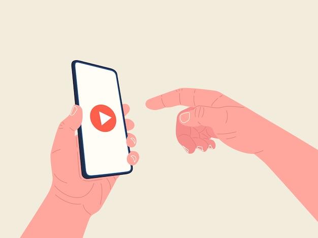Die hand hält das smartphone und die andere hand erreicht den bildschirm, um das video zu starten. videoplayer auf dem bildschirm Premium Vektoren