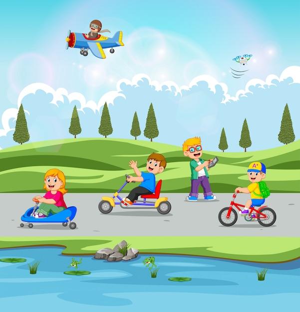 Die kinder spielen und fahren fahrrad mit der schönen aussicht Premium Vektoren