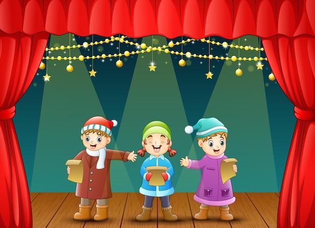 Drei kinder singen weihnachtslieder auf der bühne Premium Vektoren