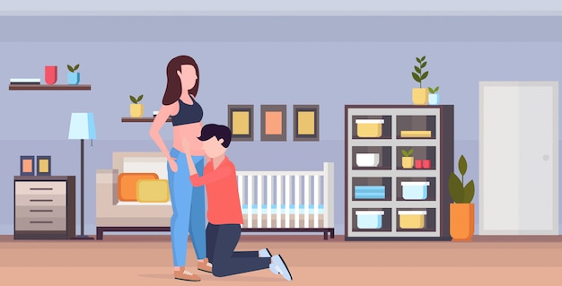 Ehemann auf dem knie hört dem bauch seiner schwangeren frau fröhliche familie zu, die neugeborenenbabyschwangerschafts-elternschaftskonzept des modernen kinderschlafzimmers innen horizontal in voller länge wartet Premium Vektoren