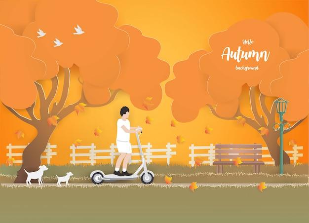 Ein junge, der einen elektroroller im park auf das gras im herbst reitet. Premium Vektoren
