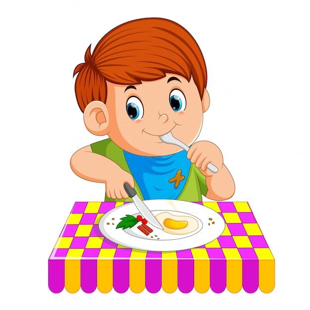 Ein junge sitzt und genießt das frühstück Premium Vektoren