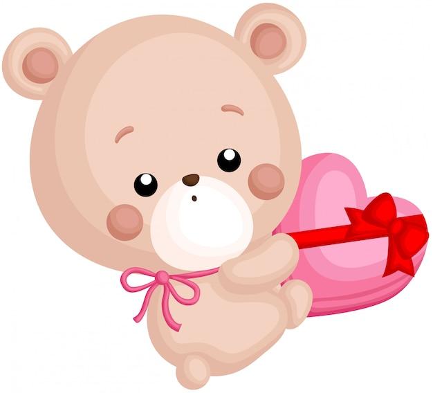 Ein vektor des netten kleinen bären, der einen schokoladen-herz-kasten hält Premium Vektoren