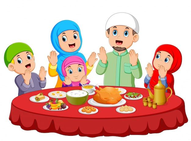 Eine glückliche familie betet für das essen auf dem ied mubarak Premium Vektoren