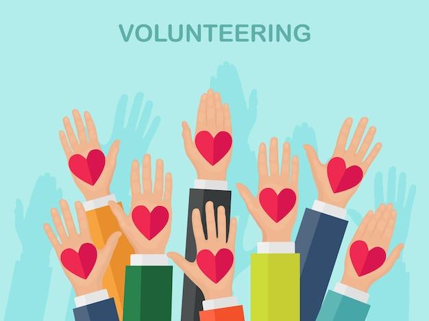 Erhöhte hände mit buntem herzen. freiwilligenarbeit, wohltätigkeit, blutspendekonzept. danke für die fürsorge. abstimmung der menge Premium Vektoren