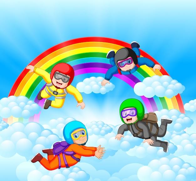 Fallschirmspringer, die spaß an der erstaunlichen wolke mit regenbogenlandschaft haben Premium Vektoren