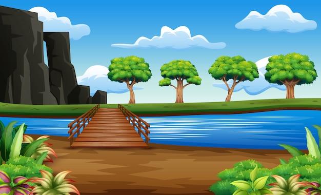 Fluss und holzbrücke in einem schönen naturhintergrund Premium Vektoren