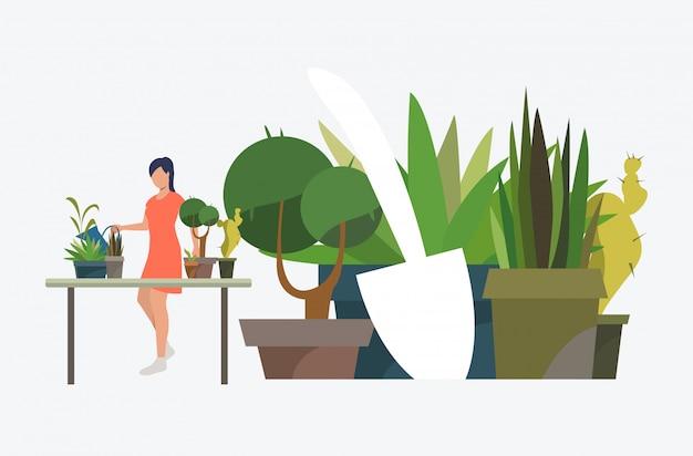Frau, die bei tisch steht und zimmerpflanzen in den töpfen wächst Kostenlosen Vektoren