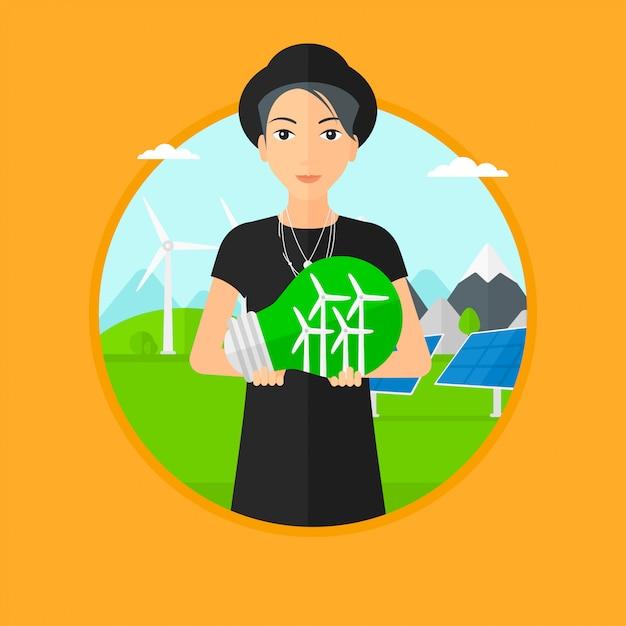 Frau, die glühlampe mit windkraftanlagen nach innen hält. Premium Vektoren