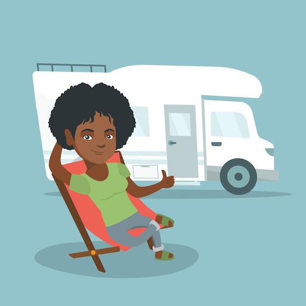 Frau, die in einem stuhl vor reisemobil sitzt. Premium Vektoren