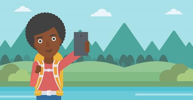 Frau mit dem rucksack, der selfie macht. Premium Vektoren