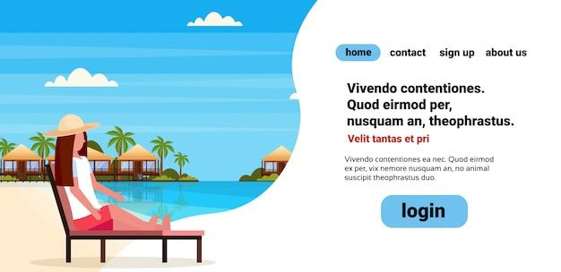 Frau sitzt sonnenliege liegestuhl auf tropeninsel villa bungalow hotel strand küste grün palmen landschaft sommer ferien wohnung copyspace Premium Vektoren