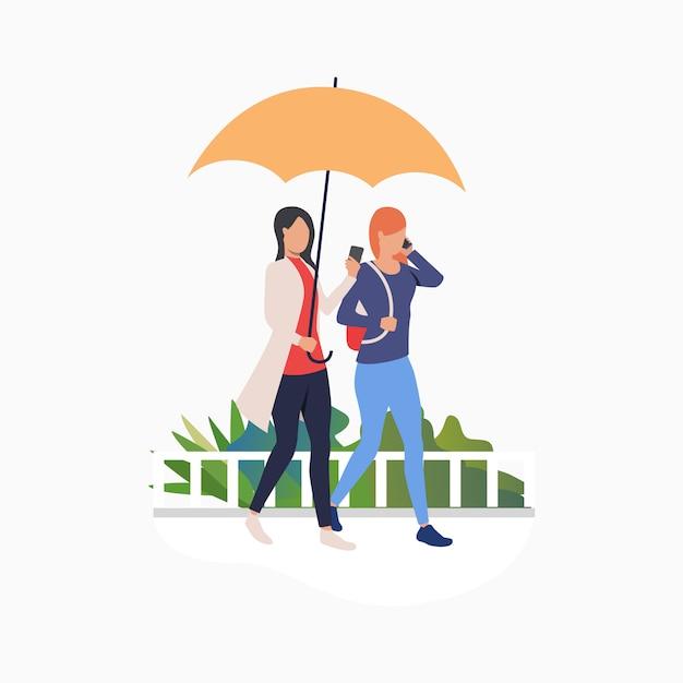 Frauen, die unter regenschirm gehen und smartphones verwenden Kostenlosen Vektoren