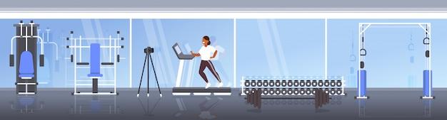 Frauenblogger, der auf tretmühlenaufnahmevideo mit kamera auf stativsozialem netz bloggt das moderne horizontale turnhalleninnere des gesunden lebensstilkonzeptes in voller länge läuft Premium Vektoren
