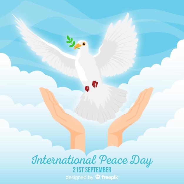 Friedenstageshintergrund mit der hand, die weiße taube freigibt Kostenlosen Vektoren