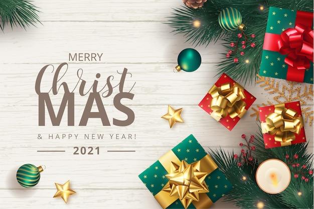 Frohe weihnachten hintergrund mit realistischen ornamenten und geschenken Kostenlosen Vektoren