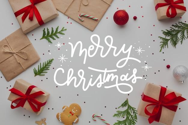 Frohe weihnachten-schriftzug auf foto mit geschenken Kostenlosen Vektoren
