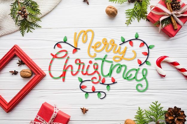 Frohe weihnachten-schriftzug mit rahmen und geschenken Kostenlosen Vektoren