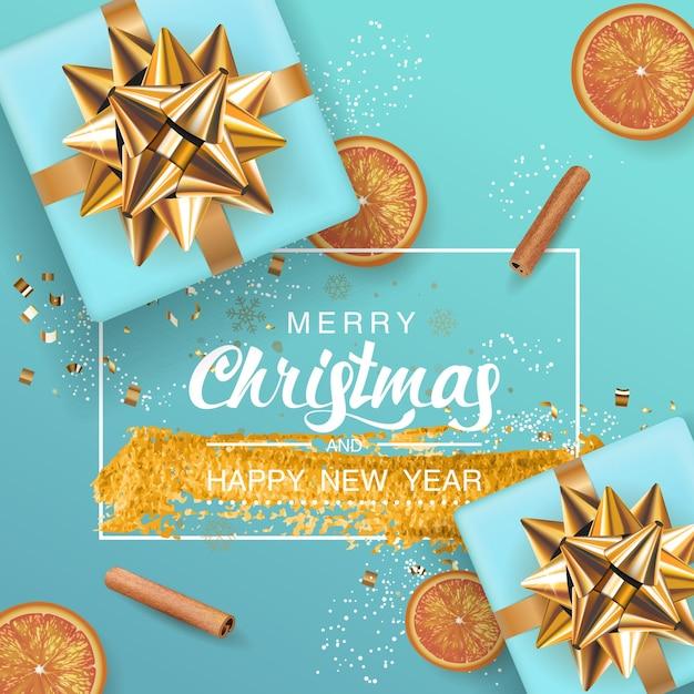 Frohe weihnachten und frohes neues jahr blauer hintergrund mit realistischer blauer geschenkbox, orangenfrucht, zimtstange. rahmenbeschriftung mit pinselspritzer goldfarbe. Premium Vektoren