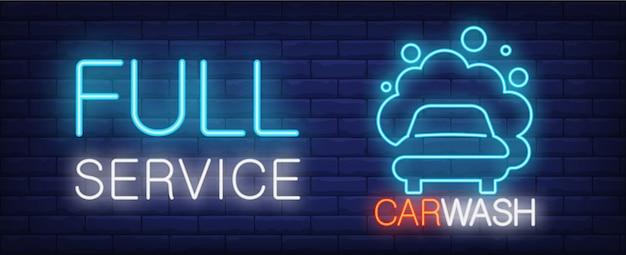 Full-service autowasch leuchtreklame. fahrzeug in schaum und leuchtende inschrift auf backsteinmauer. Kostenlosen Vektoren