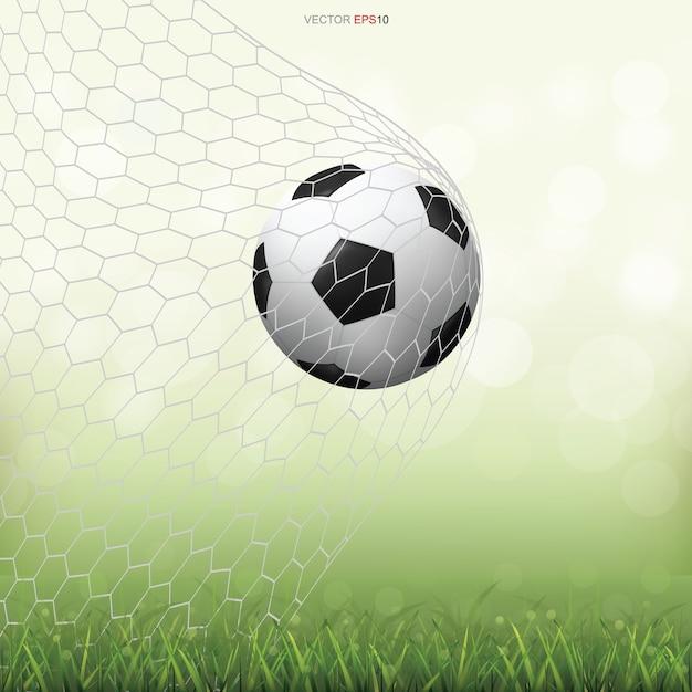 Fußballfußball auf grünem rasenfeld mit leichtem unscharfem bokehhintergrund Premium Vektoren