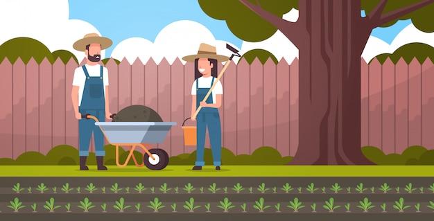 Gärtner mann mit schubkarre der erde frau hält hacke und eimer paar bauern pflanzen rüben pflanzen gemüse garten konzept in voller länge hinterhof ackerland hintergrund horizontal Premium Vektoren