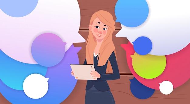 Geschäftsfrau holding tablet sprechen über bunten chat-blasen Premium Vektoren