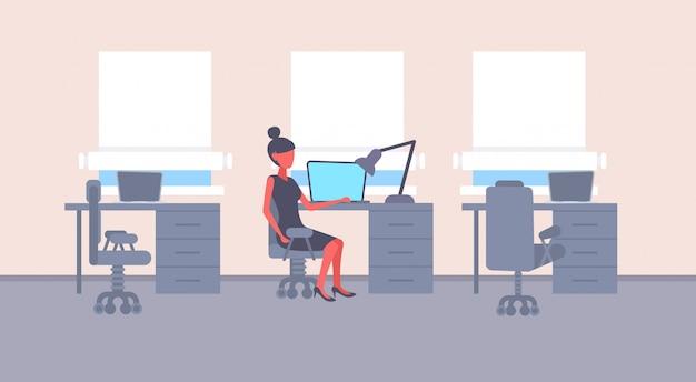 Geschäftsfrau sitzen schreibtisch arbeitsplatz geschäftsfrau arbeiten laptop weibliche zeichentrickfigur moderne büroeinrichtung flach horizontal Premium Vektoren