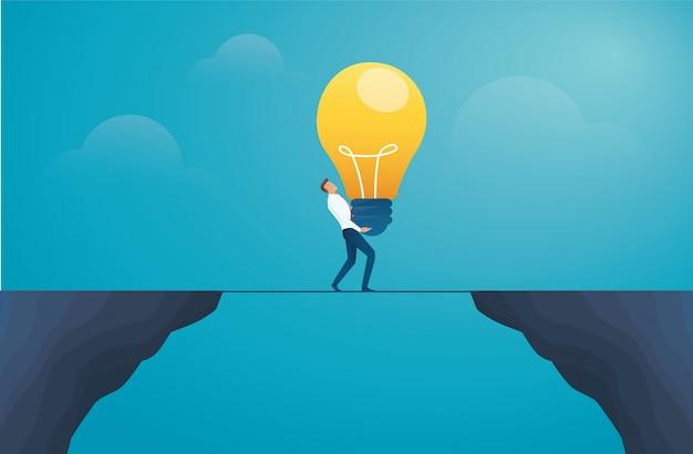 Geschäftsmann, der glühlampe hält und den berg kreuzt Premium Vektoren