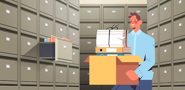 Geschäftsmann hält pappkarton mit dokumenten im aktenwandschrank mit offener schublade datenarchivspeicher business administration papierarbeitskonzept horizontale porträtvektorillustration Premium Vektoren