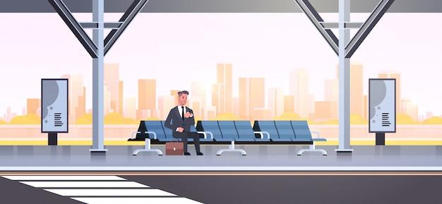 Geschäftsmann sitzen modernen bushaltestelle geschäftsmann mit koffer, der öffentliche verkehrsmittel auf flughafenstationsstadtbild wartet Premium Vektoren