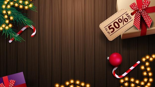 Geschenk mit tag-preis, zuckerstange, weihnachtsbaumast, weihnachtsball und girlande auf holztisch, draufsicht. hintergrund für rabattfahnen Premium Vektoren