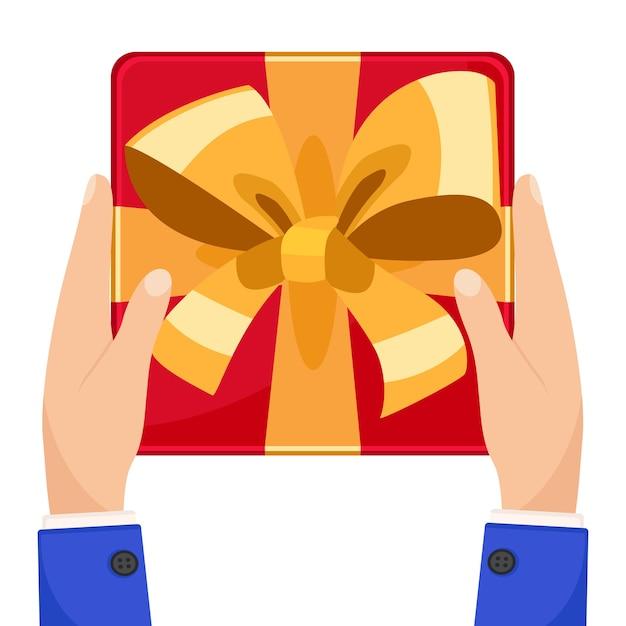 Geschenkbox mit bogen in der hand auf weißem hintergrund. der blick von oben. Premium Vektoren