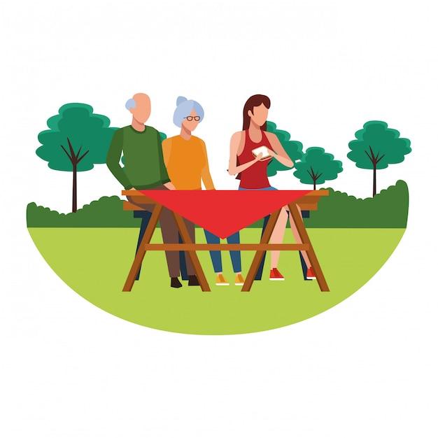 Gesichtslose familie, die tabelle im freien isst Premium Vektoren